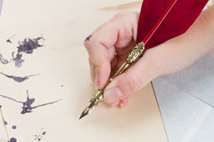 Hand holding feather pen Stock Image