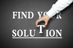 Hand holding find your solution concept. Find your solution concept with businessman hand holding against blackboard background Royalty Free Stock Photo