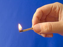A hand holding a fired matchstick royalty free stock images