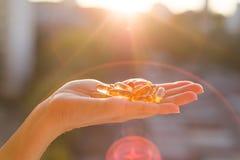Free Hand Holding Fish Oil Omega-3 Capsules, Urban Sunset Background. Stock Images - 102589534