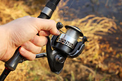 Hand Holding Fishing Pole And Fishing Reel Royalty Free Stock Photo
