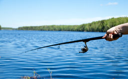 Hand holding fishing rod. Over the water Stock Images