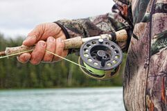 Hand holding fishing rod Stock Images