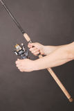 Hand holding a fishing rod. Man`s hand holding a fishing rod on a black background Royalty Free Stock Image