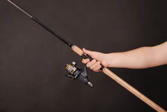 Hand holding a fishing rod. Man`s hand holding a fishing rod on a black background Stock Photo