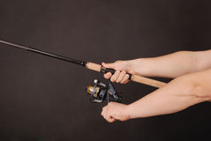 Hand holding a fishing rod. Man`s hand holding a fishing rod on a black background Stock Photos