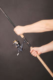 Hand holding a fishing rod. Man`s hand holding a fishing rod on a black background Stock Photography