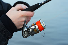 The hand holding the fishing rod Stock Photos