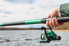 Hand holding a fishing rod with ree Stock Photos