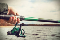 Hand holding a fishing rod with ree Royalty Free Stock Photography