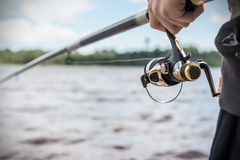 Hand holding a fishing rod with reel Stock Photography