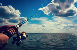 Hand holding a fishing rod with reel. Focus on Fishing Reels. Toned image Stock Image