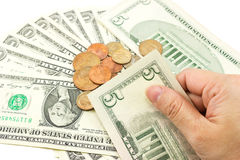 Hand holding a five dollar bill. Hand holding dollar bills with coins and dollar bill are background Stock Photo