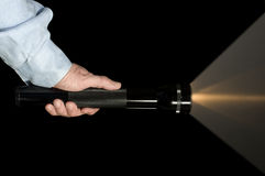 Hand holding flashlight. Security or Law Enforcement holding a Flashlight in the dark Stock Image
