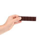 Hand holding foiled dark chocolate bar. Royalty Free Stock Photography