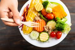 Hand holding fork and eating vegetables salad. Healthy food, top view Stock Images