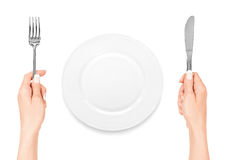 Hand holding fork and knife with plate Royalty Free Stock Photos