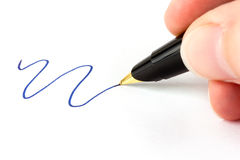 Hand holding fountain pen with blue ink Stock Image