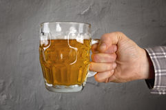 Hand holding fresh light beer making a toast. Hand holding fresh light beer making a toast, over a grunge background Stock Photos