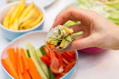 Hand holding fresh spring roll with vegetable filling. On white plate against vibrant background of vegetables Stock Image