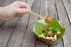 Hand holding Fried fish patty on banana leave vessel Royalty Free Stock Photos