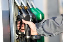 Hand holding a fuel nozzle Royalty Free Stock Images