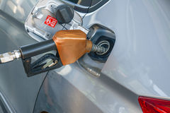 Hand holding fuel nozzle and refuel car royalty free stock photo