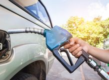 Hand holding fuel nozzle refueling gas pump for car. At gas service station Royalty Free Stock Photography