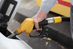 Hand holding fuel pump nozzle and refilling car Royalty Free Stock Photography