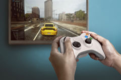 Hand holding game console controller playing game Stock Photo