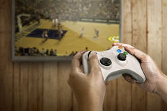 Hand holding game console controller playing game Royalty Free Stock Images
