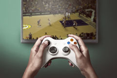 Hand holding game console controller playing game Royalty Free Stock Photography