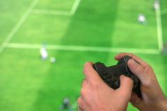 Hand holding game controller playing football game. Stock Photo