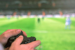 Hand holding game controller playing football game. Stock Images
