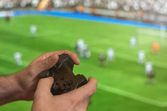 Hand holding game controller playing football game. Royalty Free Stock Image