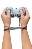 Hand holding game controller and tied up with cables isolated on Stock Photos