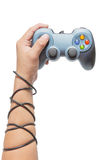 Hand holding game controller and tied up with cables Royalty Free Stock Photo