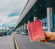 hand holding generic passport with out of focus airport entranceway. In the background Stock Images
