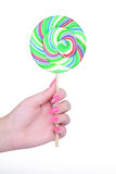 Hand holding giant colorful lollipop isolated on white Stock Photography