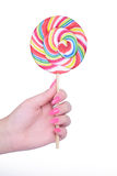Hand holding giant colorful lollipop isolated on white Stock Photo