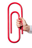 Hand holding giant paper-clip Royalty Free Stock Images
