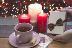 Hand holding a a gift box, a cup of tea, burning candles royalty free stock photos