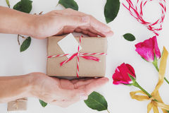 Hand holding gift box, valentines day preparing gift on white table Royalty Free Stock Photography