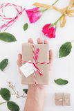 Hand holding gift box, valentines day preparing gift on white table Royalty Free Stock Photos