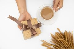 Hand holding gift box on white background stock photography