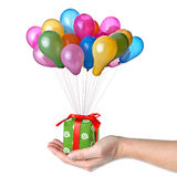 Hand holding gift with color balloons Stock Photos