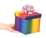 Hand holding gift in colorful package Royalty Free Stock Images
