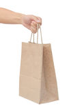 Hand holding and giving paper bag isolated over white background Royalty Free Stock Images