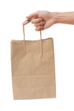Hand holding and giving paper bag isolated over white background Stock Photography