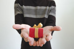 Hand holding, giving or receiving gift box, shallow depth of field, selective focus on gift box, on white background. Hand holding, giving or receiving gift box stock images